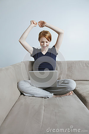 Victorious Young Woman Using Laptop