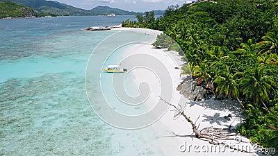 Vidéo de 4k de ralenti de plage exotique tropicale avec un bateau solitaire amarré sur une plage de sable blanc parfait et turquo banque de vidéos