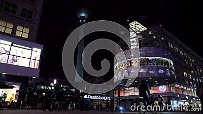 Vidéo nocturne de l'horloge mondiale, cyclistes et personnes à Alexanderplatz avec la tour de télévision et la gare banque de vidéos