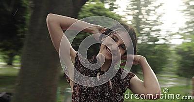 Video de mujer alegre y atractiva girando sobre un columpio bajo la lluvia Una chica sonriente con el pelo corto se divierte en e metrajes