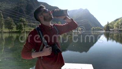Hiker young man traveler with backpack drinking water while standing in front of lake. Video of hiker young man traveler with backpack drinking water while stock video
