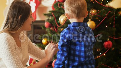 Video 4k des kleinen Jungen des Kleinkindes, der Weihnachtsbaum mit Flitter verziert stock video