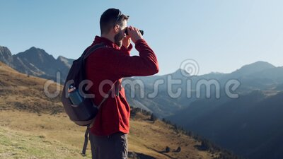 Man travel hiker enjoying the nature while looking the landscape with binoculars in the mountain. Video of man travel hiker enjoying the nature while looking stock video footage