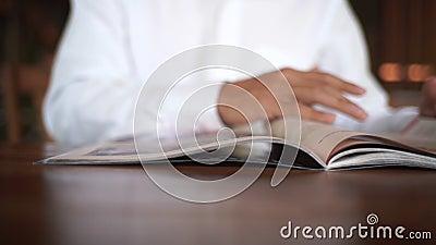 4.000 videos de un hombre de closeup leyendo el holding y la revista abierta en la sala de estar, hobby para el estilo de vida re almacen de metraje de vídeo