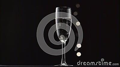 Vidrio enfriado de champán Bokeh que centella el fondo negro metrajes