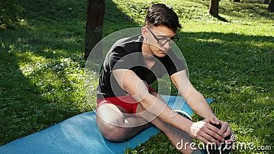 Vidrios que llevan atractivos del hombre joven que estiran sus piernas tempranas por la ma?ana en Green Park hermoso outdoor En a almacen de metraje de vídeo