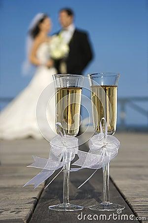 Vidros de Champagne com noiva e noivo no fundo.