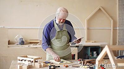 Vieil artisan dans l'uniforme fonctionnant tenant le comprimé numérique dans l'atelier banque de vidéos