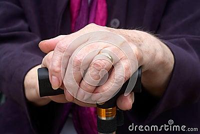 Vieilles mains sur le bâton de marche