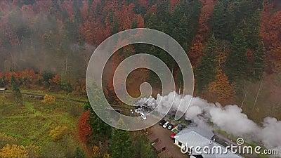 Vieja locomotora de trenes de época que se mueve por el impresionante valle del bosque en montañas, colores del otoño, tiro con d metrajes