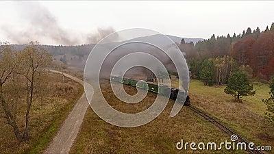 Vieja locomotora de trenes de época que se mueve a través del impresionante ferrocarril forestal, paisaje montañoso, colores otoñ almacen de metraje de vídeo
