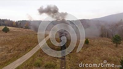 Vieja locomotora de trenes de época que se mueve a través del impresionante ferrocarril forestal, paisaje montañoso, colores otoñ almacen de video