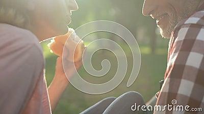 Viejo hombre juguetón y mujer que se relajan en parque y que comen la hamburguesa, fin de semana, primer metrajes
