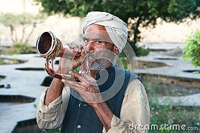 Viejo hombre musulmán con el turbante que sopla una trompeta Foto editorial