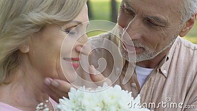 Viejo hombre que trae el ramo de flores a la mujer y que la abraza blando con amor almacen de metraje de vídeo
