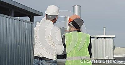 Viejo ingeniero y su asistenta mujer de etnia africana analizando el plan de construcción en la azotea del edificio almacen de metraje de vídeo