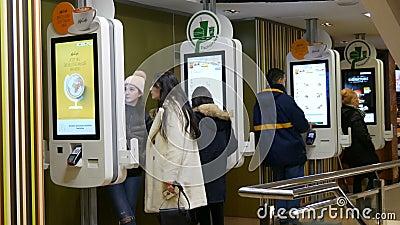 Viena, Austria - 19 de diciembre de 2019: Pantalla digital para pedidos sin cajeros en McDonalds La gente hace comida rápida almacen de video