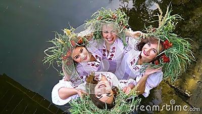 Vier gelukkige meisjes in bloemenkringen en geborduurde jurken die in water poseren stock video