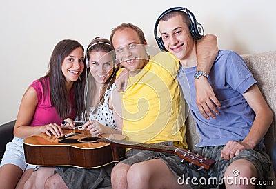 Vier jonge mensen met gitaar en hoofdtelefoons