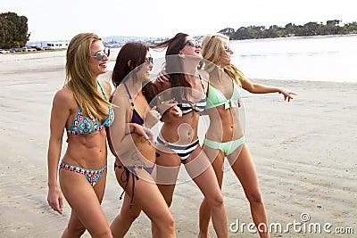 Vier schöne junge Frauen, die den Strand genießen