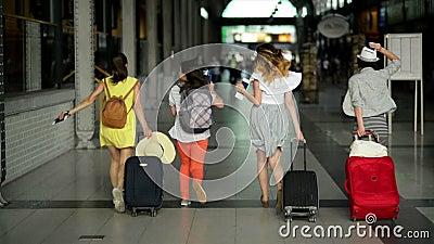 Vier vrouwelijke vrienden in heldere de zomerkleding zijn laat voor hun vliegtuig De mooie meisjes lopen binnen de luchthaven stock video