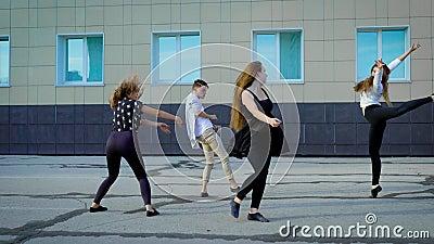 Vier zeitgenössische Tänzer probt modernen Tanz auf einer Straße vor Gebäude in der Tageszeit stock video