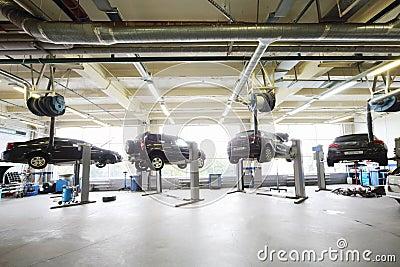 vier zwarte auto 39 s die op liften in garage worden