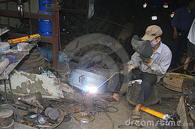 Vietnamese welder on the sidewalk Editorial Photography