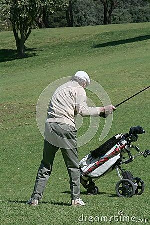 Vieux golfeur et chariot