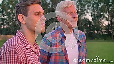 Vieux père étreignant le fils adulte et regardant en avant, se tenant sur le champ de blé ou de seigle, forêt à l'arrière-plan banque de vidéos