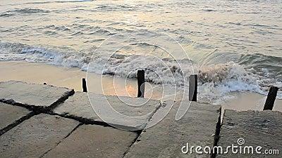 Vieux remblai en béton avec les poteaux en bois contre le contexte des vagues de mer avec un chemin ensoleillé le soir banque de vidéos