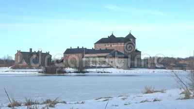 View of the ancient fortress of Hameenlinna, March afternoon. Finland. View of the ancient fortress of Hameenlinna on the shore of a frozen lake Vanajavesi stock video