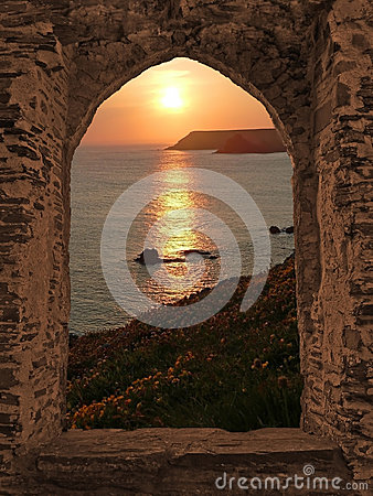 View through arched castle window to sunset coastal landscape, c