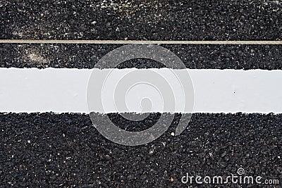 View of asphalt with distinct white stripes.