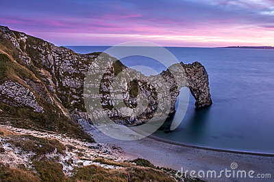 View of Durdle Door in United Kingdom at Sunset.