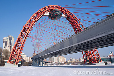 View of red arc bridge on frozen river and houses