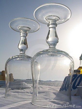 View of sailboat through wine glasses, Mykonos, Greece
