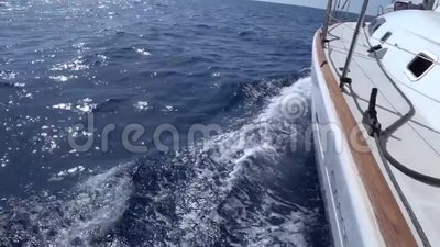 A view from the yacht`s deck to the bow and sails, close-up S ide view with  blue sea and waves