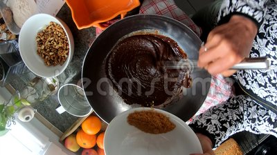 Viftar blandande ingredienser f?r kvinna f?rbi f?r att laga mat bagerit f?r chokladkakan arkivfilmer