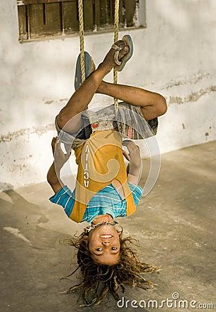 A village boy hanging upside down