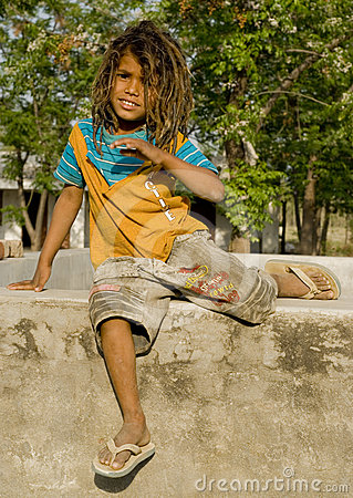 A village boy sitting on a small wall