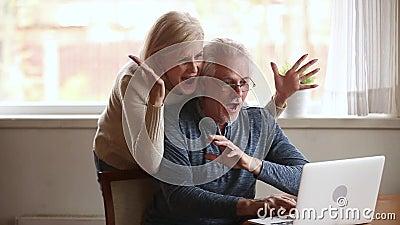 Vincitori senior emozionanti delle coppie che per mezzo del computer portatile estatico dalla vittoria online stock footage