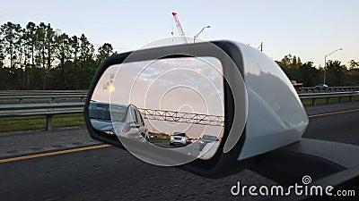 Vingspegel av en bil som på flyttar huvudvägen lager videofilmer