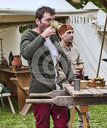 Vino de consumición del hombre medieval Foto de archivo editorial