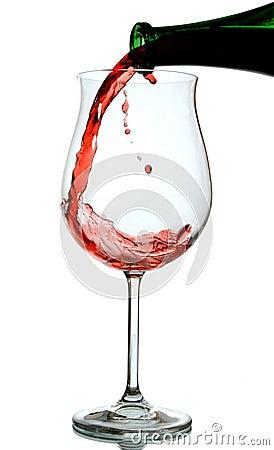 Vino rosso che è versato in un vetro di vino