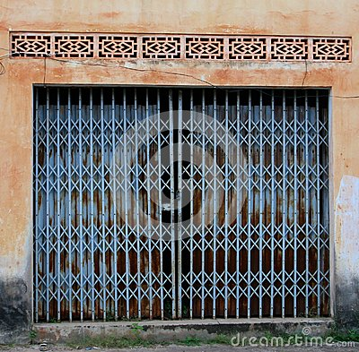 Vintage blue doors in a grungy wall, French colonial style, Laos