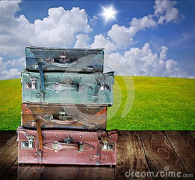 Vintage luggage on wooden table with nice landscape background