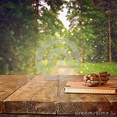 Free Vintage Notebook And Stack Of Wooden Colorful Pencils On Wooden Texture Table In Front Of Countryside Forest View Royalty Free Stock Photography - 59231097