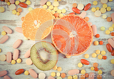 Vintage photo, Fresh fruits and colorful medical pills, choice between healthy nutrition and medical supplements