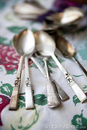 Vintage silver spoons on an antique tablecloth